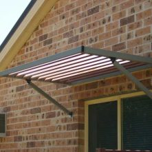 arm supported aluminium awning on brick wall